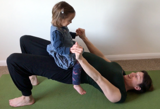 Yoga2shape kids' yoga class. Kat Frost balances two year old child on hips as she does Bridge Pose in a YogaShapes class