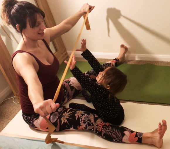 Kat Frost, Yoga2shape, sits in upavista konasana (wide angle pose) holding a ribbon for the two year old toddler to grab.