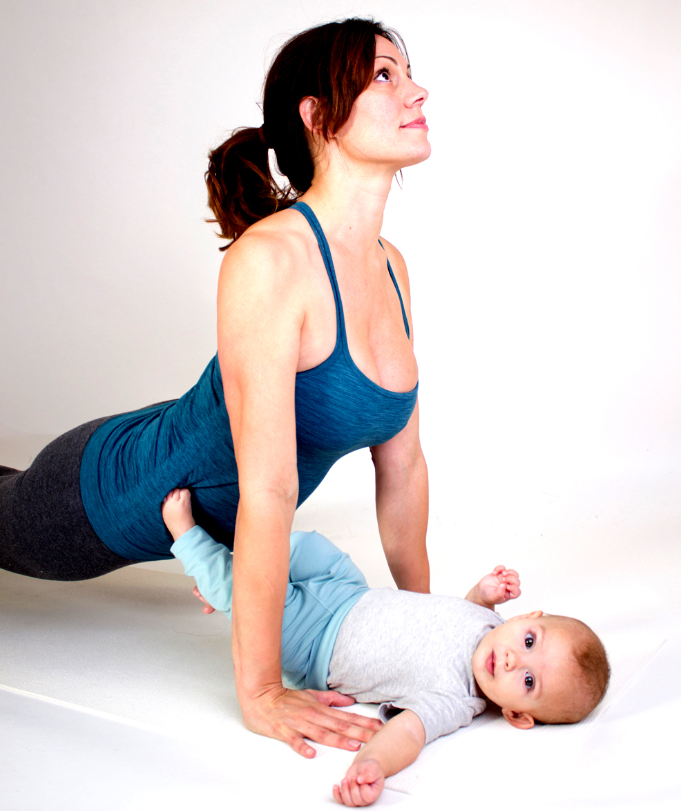 A yoga teacher does upward facing do in a mum and baby yoga class in Whiteley, Hampshire