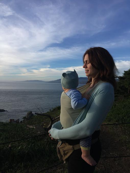 Mother wears baby in sling